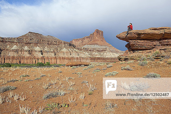 A woman sits on a bedrock terrace at Saddle Horse Bottom below tall canyon walls in Canyonlands National Park  Utah.