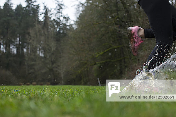 Woman Running Through A Puddle In A Grassy Yard