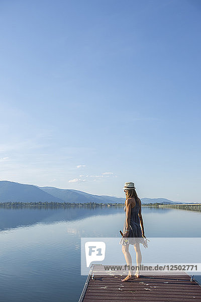 Woman Standing On The Edge Of Wooden Dock Overlooking Lake Pend Oreille  Sandpoint  Idaho