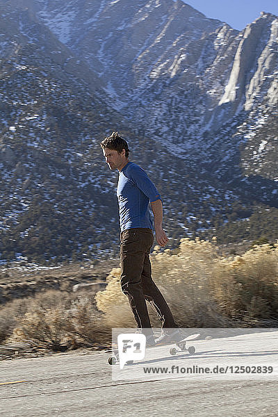 Adult man skateboarding at foot of mountains in Sierra Nevada Mountains