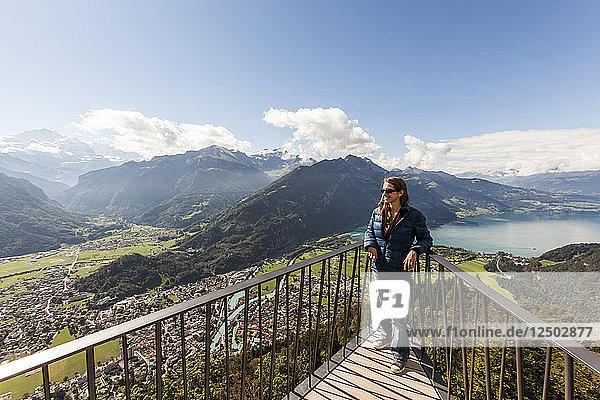 Young woman enjoying the view from the Harder Klum in Interlaken  Switzerland in the Alps.