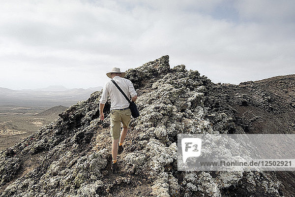 A Man Stands On Top Of A Volcanic Rock
