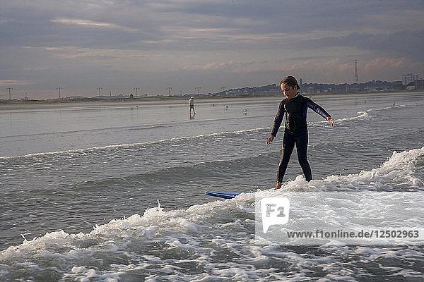 A Boy Surfs At Nahant Beach In Nahant  Massachusetts