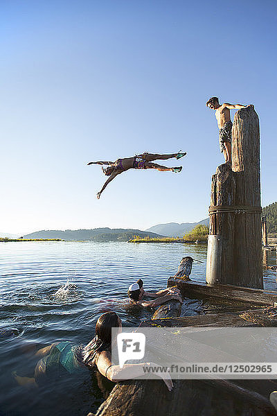 A group of friends jumping and playing in the water. Lake Pend Oreille  Sandpoint  Idaho.