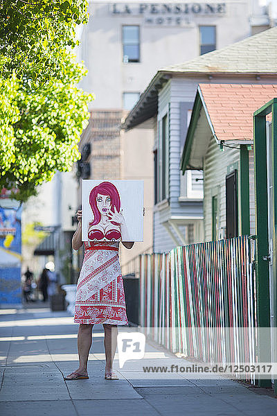 A woman holding a bust-up painting in front of herself in San Diego's Little Italy.