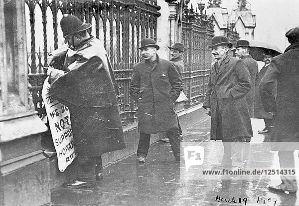 A policeman removes a suffragette poster from the railings  House of Commons  London  March 1909. Artist: Unknown