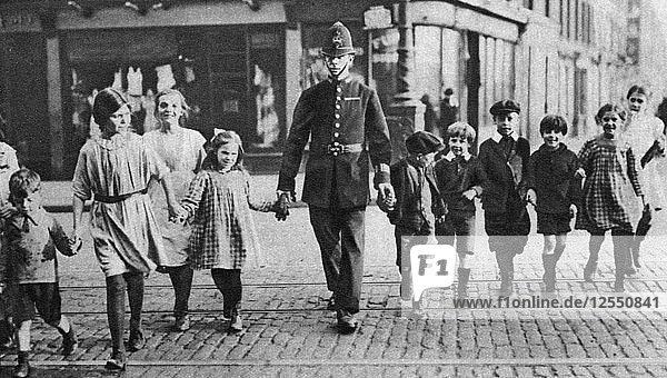 Policeman helping schoolchildren across the road  East End  London  1926-1927. Artist: Unknown