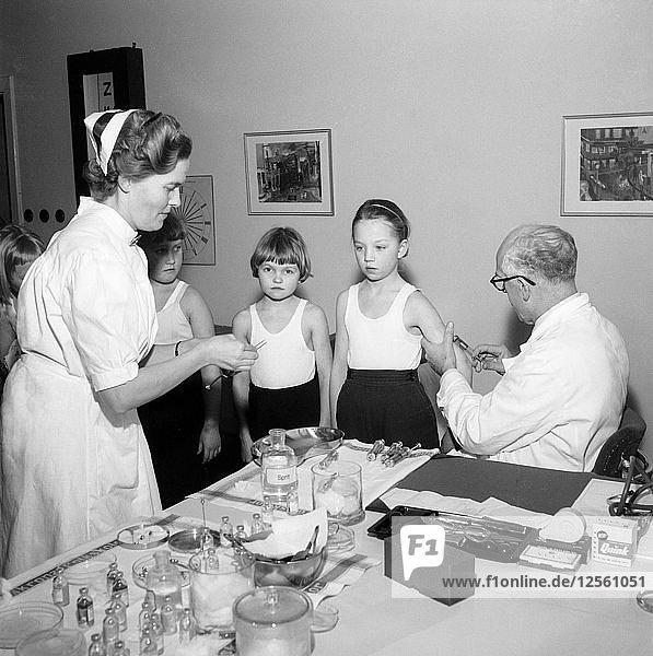 A doctor and his nurse vaccinate schoolgirls againgst polio  Landskrona  Sweden  1957. Artist: Unknown