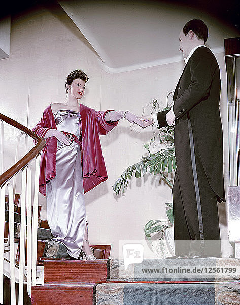 Female model shows an evening dress  with a male model in a tailcoat  Sweden  1950s. Artist: Göran Algård