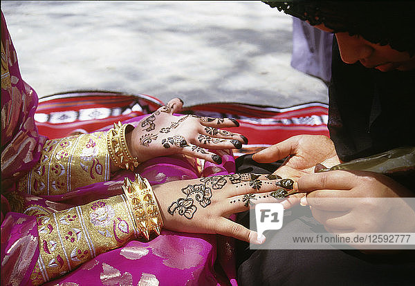 Geometric and floral decorative henna patterns were applied to adorn the hands and feet of young women on occasions such as weddings.
