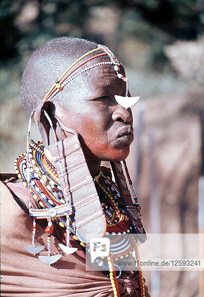 The elaborate beadwork of this Masai woman indicates her ethnic identity  social status  and the number and status of her children.