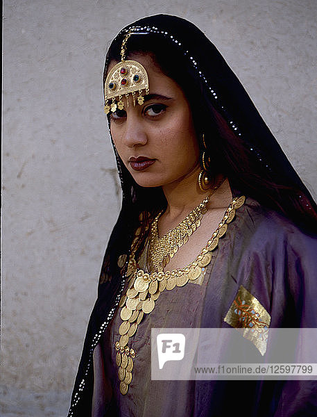 A woman wearing impressive gold jewellery and traditional costume.