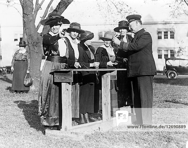 Police officer teaching women how to shoot  c. 1920.