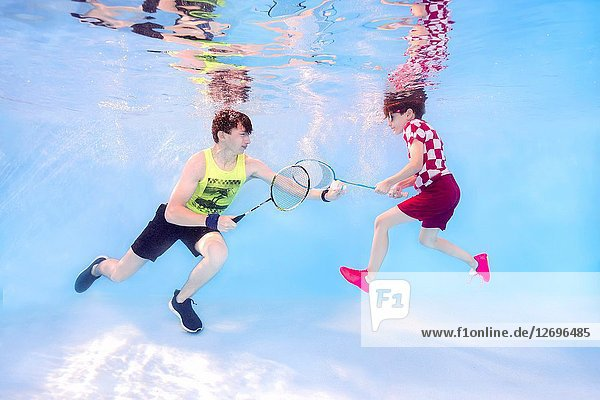 Two teenagers playing badminton underwater.