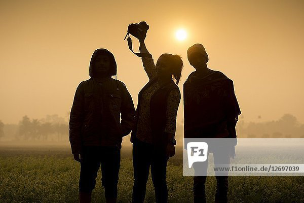 Silhouette of woman photographer and his friends at sunrise time.