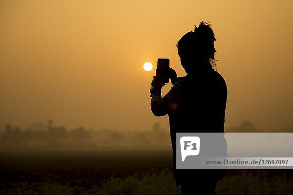 Silhouette of the photographer. Photo shooting during amazing sunrise on the village of Bangladesh.