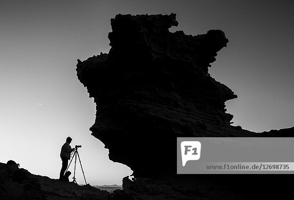 Rock and photographer shape at Formentera,  Balearic Islands,  Spain.