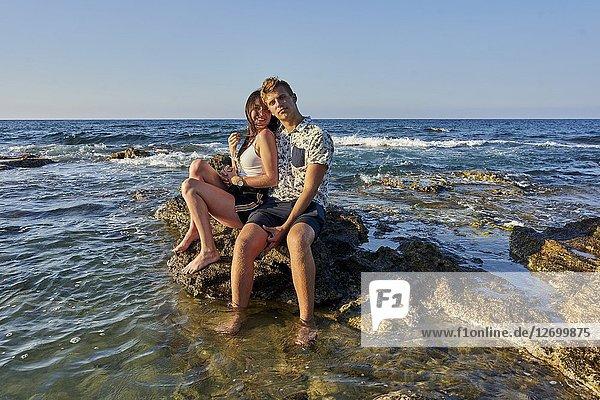 Couple sitting on rocks in sea  vacations  love. Chersonissos  Crete  Greece.