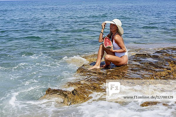 Woman with water melon and sunhat sitting on rock in sea  Chersonissos  Crete  Greece.