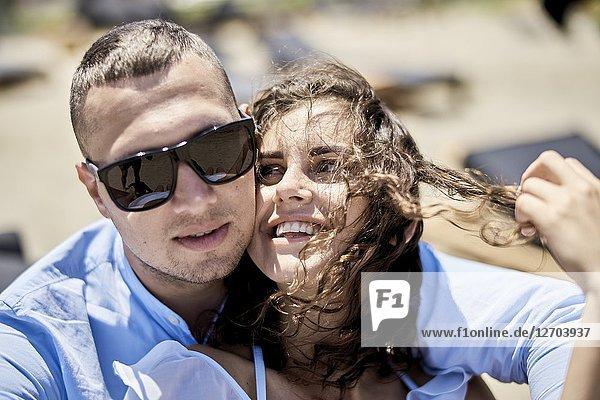Man embracing woman  on sunbeds  vacations  love  affair  sensual  couple  flirt  summer