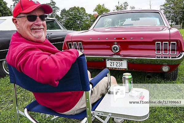 Goshen  Connecticut USA A man in red sits next to his red Mustang car at the annual classic car show at the Litchfield County Fairgrounds.