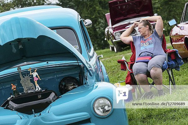 Goshen  Connecticut USA A women fixes her hair next to a classic car with a statue of liberty  at the annual classic car show at the Litchfield County Fairgrounds.