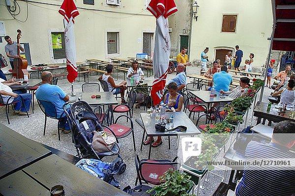 People enjoying the atmosphere and food at the village restaurant in Vrbnik on the Croatian island of Krk.