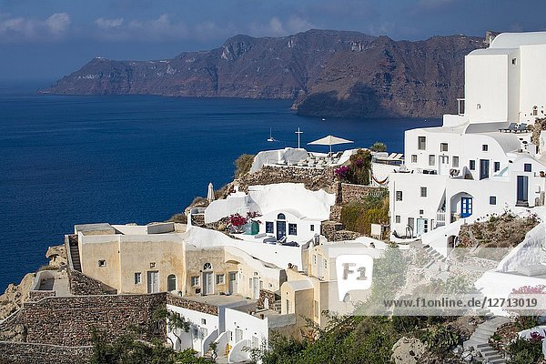 Traditional Greek flag with domed Orthodox Church overlooking the Aegean Sea in Oia Santorini Greece.