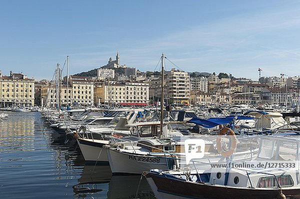 The Vieux Port (old port) with boats in Marseille  France with the Notre-Dame de la Garde (Our Lady of the Guard)  a Catholic basilica in the background.