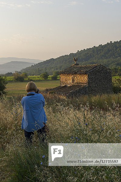 A woman is photographing a small house in a valley near the village of Gordes in the Luberon  Provence-Alpes-Cote d Azur region in southeastern France.