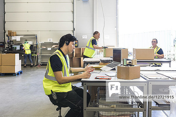 Young customer service representative talking through headset while coworkers at warehouse