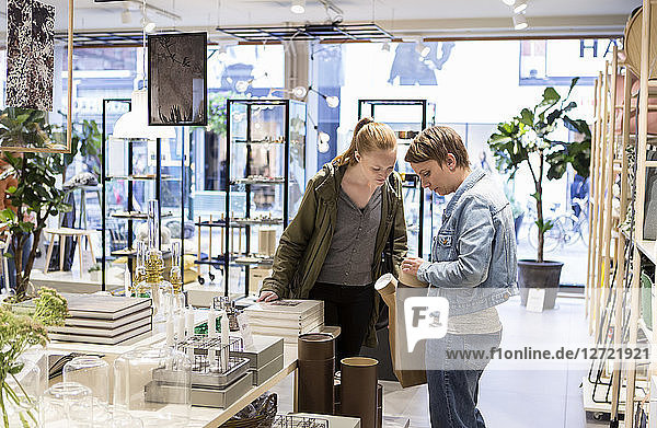 Friends standing by table with various objects at design store