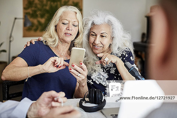 Senior woman showing mobile phone to friend while vlogging at home