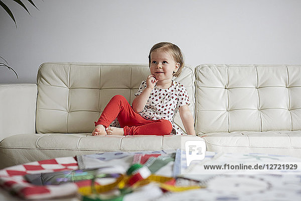 Thoughtful girl sitting on sofa at home