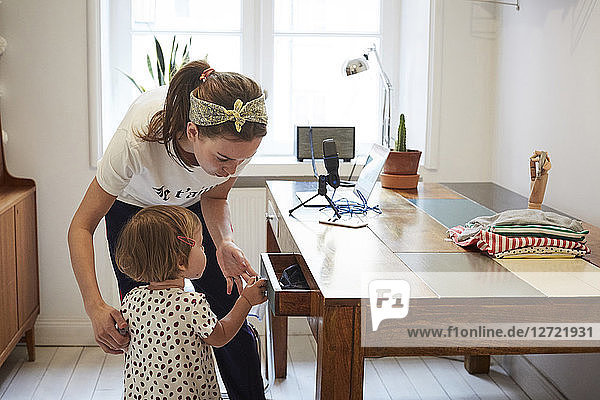 Podcaster looking at daughter opening drawer while standing by table