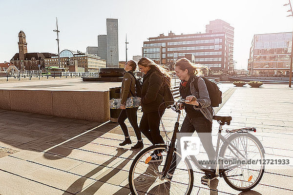 Teenage girl holding bicycle while walking with friends on pedestrian zone in city