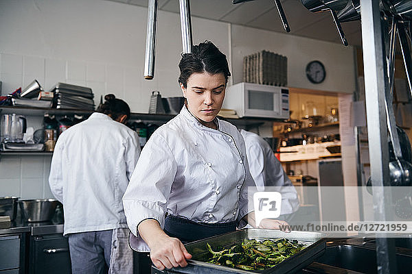 Mid adult female chef holding baking sheet with broccoli at commercial kitchen