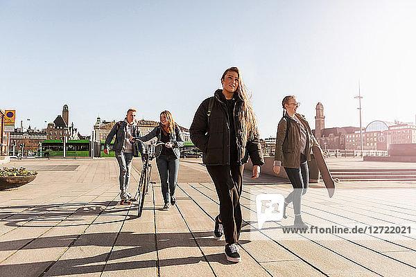 Teenagers walking on footpath against clear sky in city