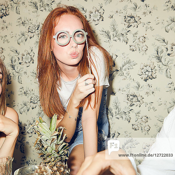 Portrait of young redhead woman holding eyeglasses prop while sitting amidst friends during dinner party at home