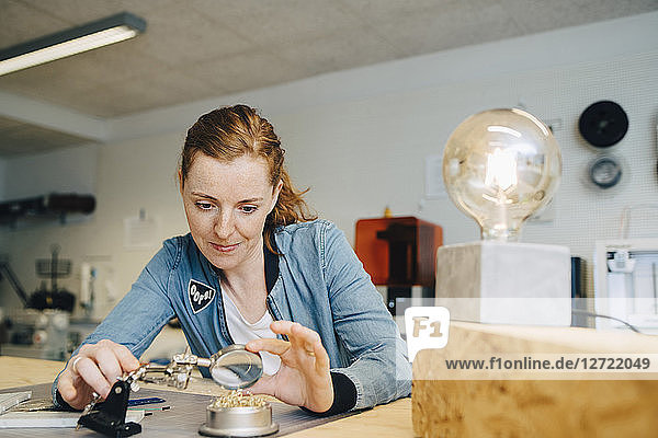 Confident redhead female engineer looking through magnifying glass at workbench in creative office