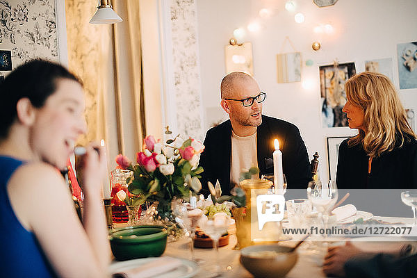 Mature friends talking while enjoying food at dinner party