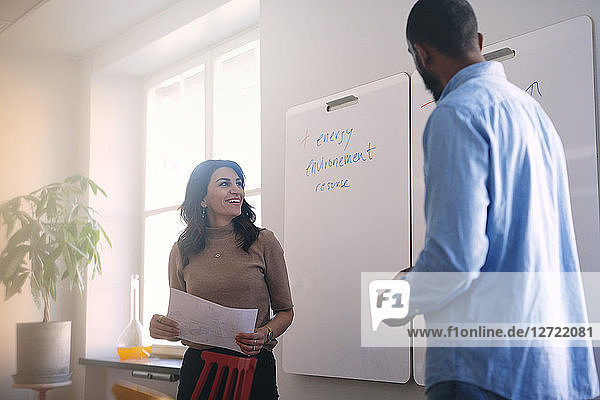 Male and female engineers standing while reading text on whiteboard in office