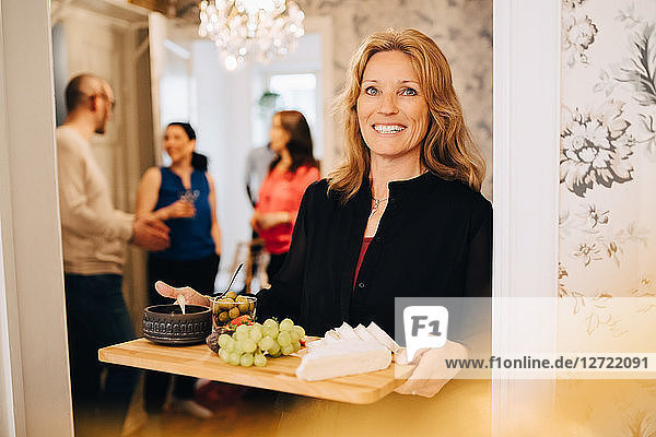 Portrait of smiling mature woman holding serving tray with friends standing in background