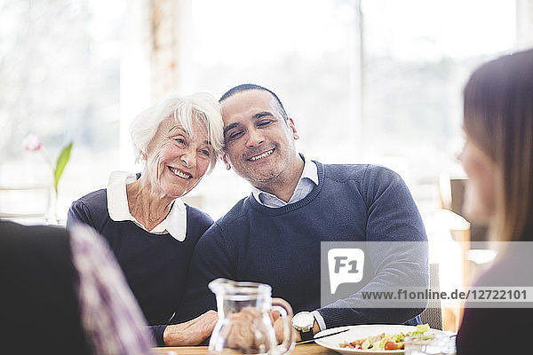 Smiling senior woman sitting with son while having lunch at table in nursing home