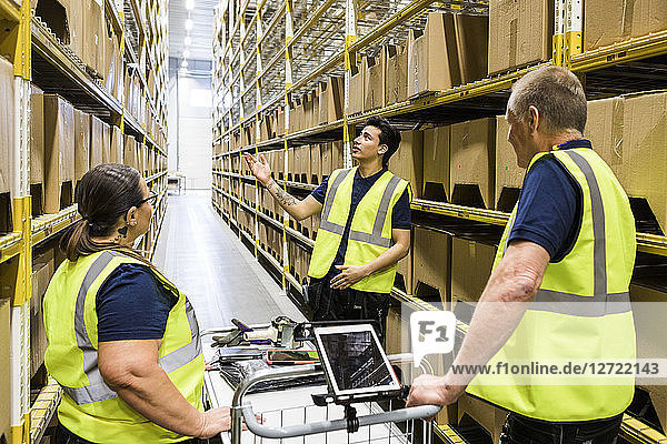 Young worker discussing with coworkers with cart while standing on aisle amidst racks at distribution warehouse