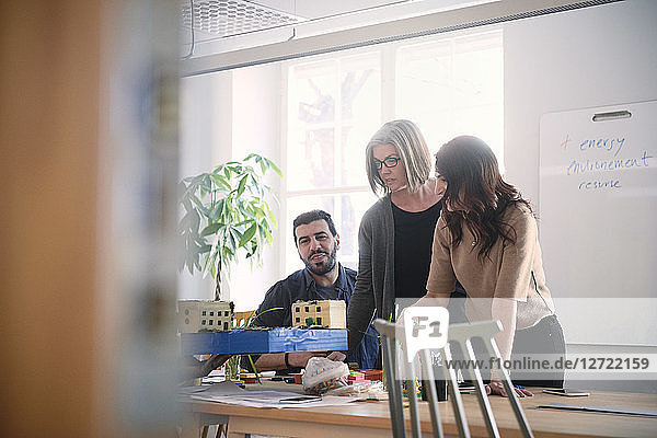 Multi-ethnic male and female engineers discussing over architectural model at table during meeting in office