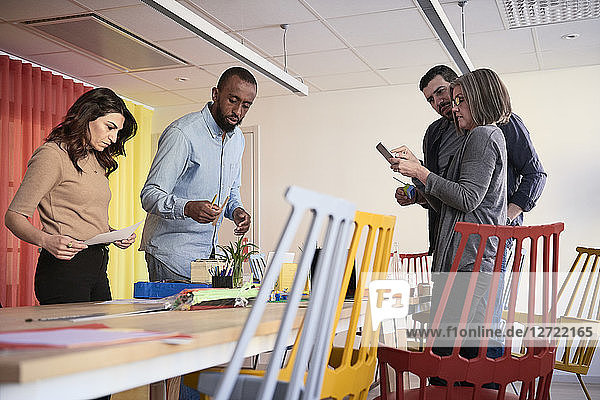 Multi-ethnic male and female engineers standing at table while working on project in office