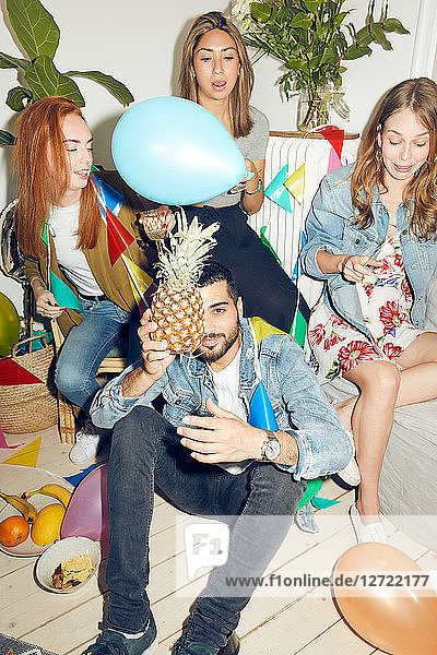 Portrait of young man holding pineapple while sitting against female friends enjoying party at home