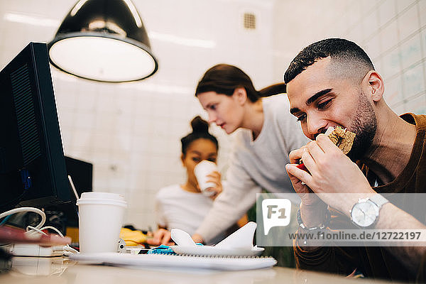 Young male hacker eating sandwich while female colleagues working during meeting at small office