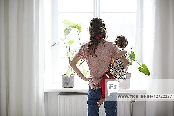 Rear view of fashion designer carrying daughter while standing at home